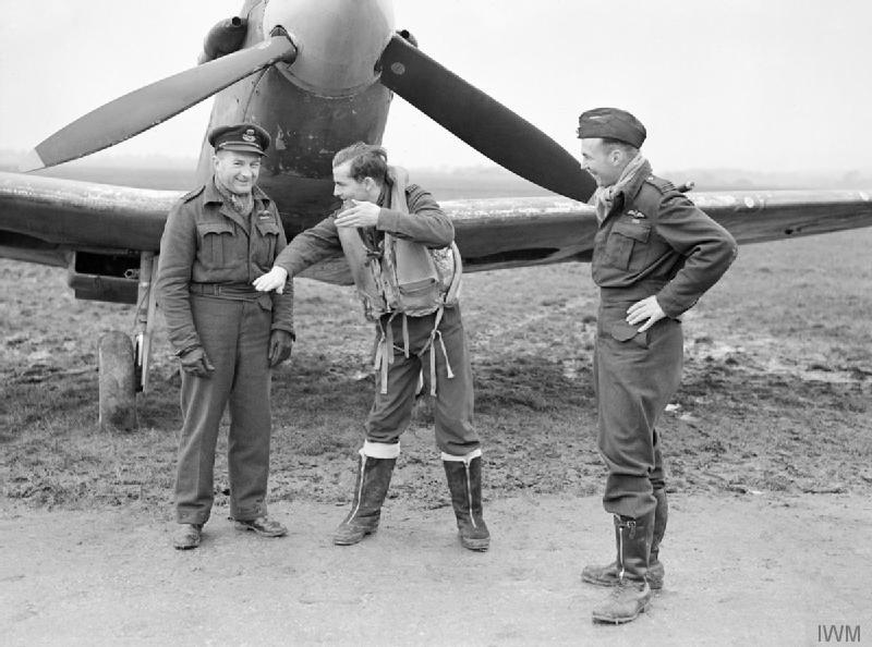 Three pilots in front of an aircraft at the Westhampnett airstrip