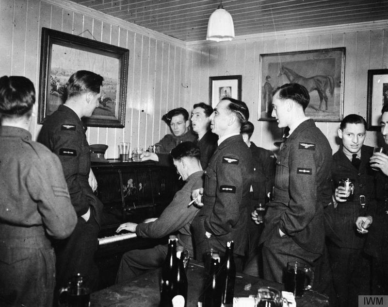 A photo of pilots drinking and playing piano in a pub.